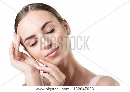Portrait of joyful young woman with closed eyes and dots of cream on her cheek. She is wearing decorative make-up and gently touching her face by hands. Isolated and copy space in right side poster