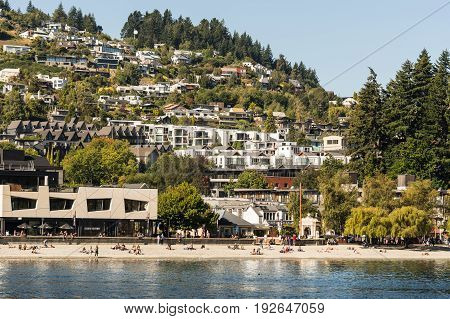 Queenstown New Zealand - March 15 2017: The sandy beach downtown on Northeast shore of Lake Wakatipu. Riviera style dense housing built on of hill. People on the beach. Green vegetation.