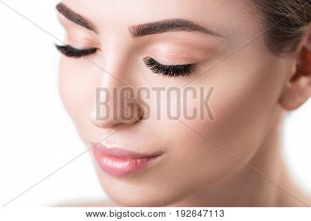 Close up of face of young happy woman with closed eyes. She is wearing decorative make-up and having long eyelashes. Isolated
