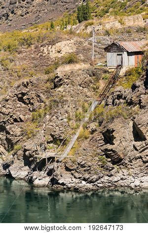 Cromwell New Zealand - March 15 2017: Historic gold fields shed and shute to Kawarau River at the gorge. Sparse vegetation on dry brown rocks and mountain. Greenish river water.