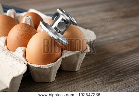 Eggs with stethoscope on wooden table
