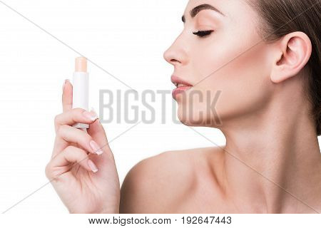Profile of joyous young woman holding lipstick in her hand in front of her face and looking at it with adoration. Copy space in left side and isolated