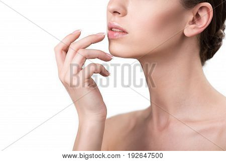 Close up of lower face with neck and hand of young attractive lady slightly touching her mouth by nails. She is wearing lip-gloss. Isolated