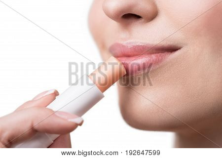 Close up of lips of happy young woman putting lip-gloss on. She is touching her lips by stick and smiling. Isolated and copy space in left side