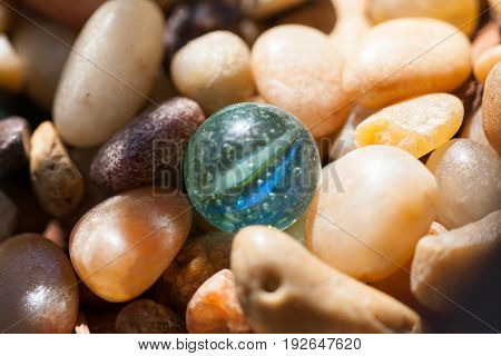An old marble with air bubbles in the glass lays among tumbled pebbles in the sunshine.