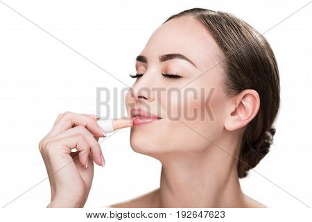Close up of head of jolly young attractive woman holding lipstick in her hand and touching it her lips with adoration. She is closing her eyes with joy. Copy space in left side and isolated