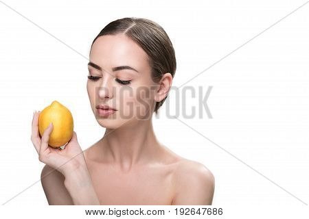 Portrait of serious young woman with perfect make-up and naked shoulders holding lemon in her hand near her face. She is looking at it with half closed eyes. Isolated and copy space in right side