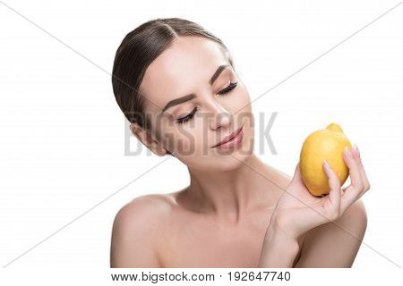 Portrait of jolly young woman holding lemon in her palm and looking at it happily with half closed eyes. She is wearing light make-up. Isolated