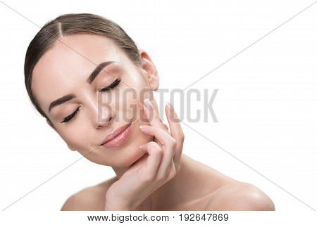 Portrait of jolly young lady with closed eyes. She is bending her head slightly aside with little smile and touching her perfect face by hand with French manicure. Copy space in right side. Isolated