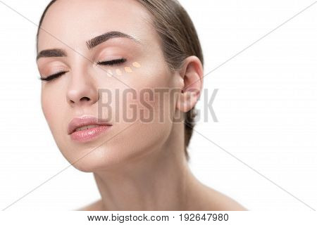 Portrait of serene young woman with closed eyes and dots of foundation under her eye. She is looking well and enjoying her make-up. Isolated and copy space in right place