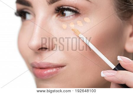 Close up of face of happy young lady applying foundation dots under eye by special brush. Isolated