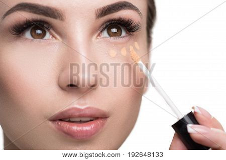 Close up of face of young pensive woman applying foundation by special applicator. She is making little dots of base under her eye. Isolated