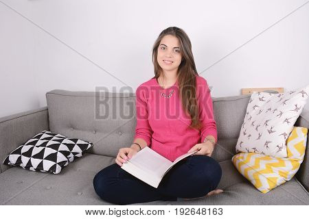 Beautiful young woman relaxed and reading a book. Indoors.