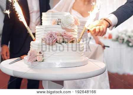 Wedding cake with flares. the waiter lights the candles fountains wedding cake