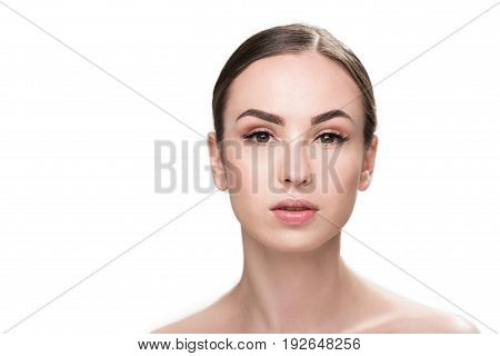 Portrait of serious beautiful young woman wearing light decorative make-up. Copy space in left side. Isolated