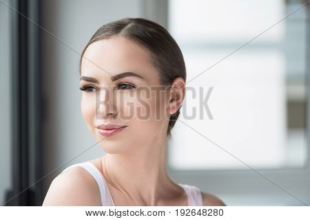 Portrait of cheerful young woman wearing perfect make up. She is looking to distance with happiness. Copy space in right side