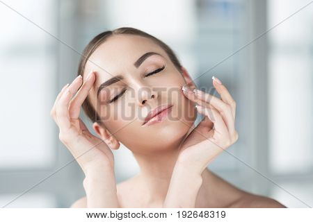 Portrait of jolly young woman enjoying her fresh make-up. She is slightly touching her face by both hands as if embracing it