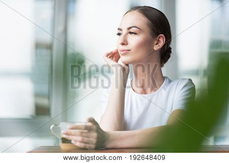 Jolly young lady with fresh make-up sitting at desk on balcony and embracing cup of coffee by her palm. She is slightly touching her face by other hand and looking to distance. Copy space in left side