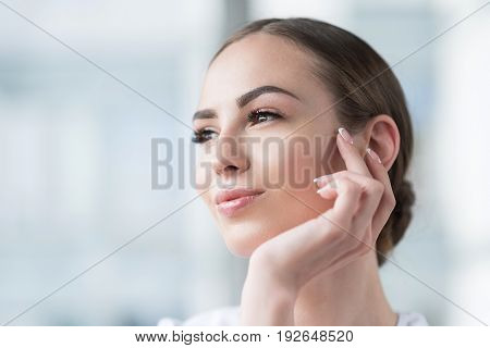 Portrait of cheery young woman with fresh make-up leaning on her palm by her chin. She is wearing French manicure on hand nails and looking far to distance with pleasure. Copy space in left side