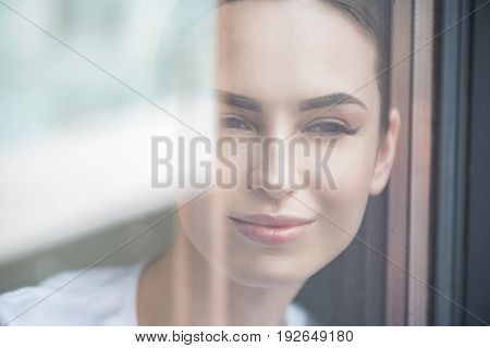 Close up of face of jolly young beautiful woman looking through window glass from home. She is wearing light make-up