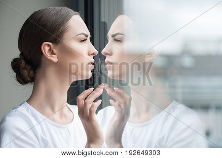 Profile of worried young woman standing by window and touching it slightly by fingers. She is looking outside with anxiety and reflecting in glass. Copy space in right side