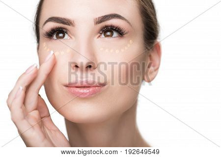 Joyful woman is applying foundation on her visage. She looking up with light smile. Portrait. Isolated
