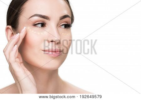 Confident woman applying foundation on her face and looking aside with light smile. Portrait. Isolated
