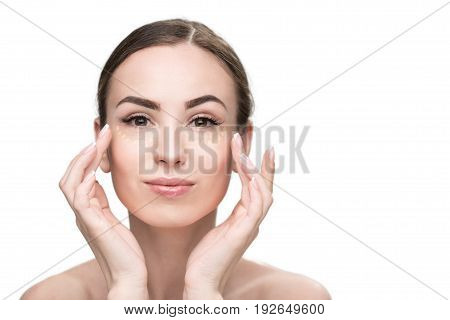 Assured girl is applying concealer on her young face and looking at camera with light smile. Portrait. Isolated