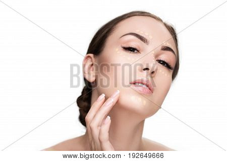 Beautiful woman is applying foundation on her face and looking at camera sensual interest. Portrait. Isolated and copy space