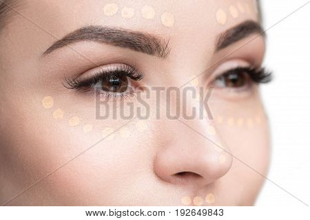 Attractive young lady is looking aside with light interest. She has foundation at skin of face. Close-up of her eyes