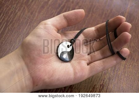 Hand holding pearl yin yang necklace on wooden background.