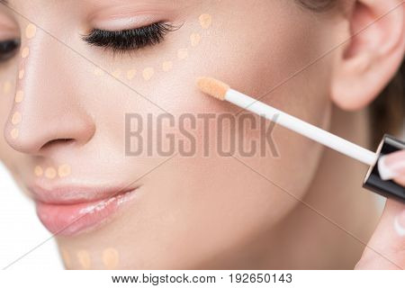 Cheerful lady is using brush for applying beige foundation on face. Close-up of female cheek