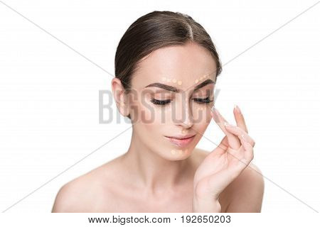 Concentrated attractive woman is applying beige foundation on her face. She looking down with light smile. Portrait. Isolated