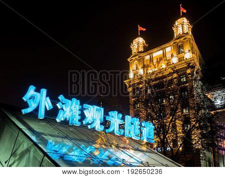 Shanghai, China - Nov 4, 2016: The Bund Tourist Tunnel (Chinese characters) entrance/exit by night. View of North China Daily News (AIA - American Insurance Association) building in background. Along The Bund on Zhongshan East 1st Road.