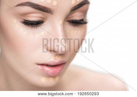 Young lovely woman has beige blobs of foundation at her visage. She looking down. Close up portrait. Isolated