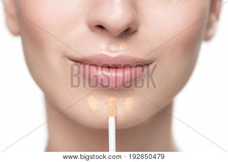 Beautiful girl with pure skin is using foundation. Close up of female chin and special cosmetic brush. Isolated