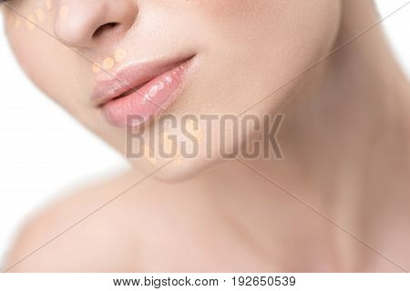 Stunner lady is using beige foundation at her pure face. Close up of lips on female visage