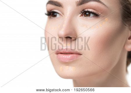Beautiful lady is using concealer at her face and looking aside with wistfulness. Portrait. Isolated. Copy space on left side