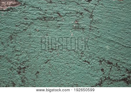 Green painted wall with cracks photo texture. Cement wall with stains and grit closeup. Rustic old surface for vintage background. Teal paint on plaster background. Distressed concrete wall close-up