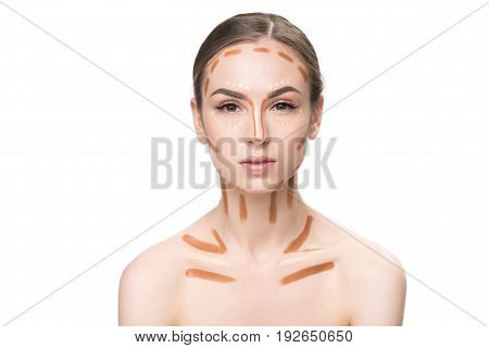 Thoughtful young lady is using concealers at face and clavicles. She looking at camera with attention. Portrait. Isolated