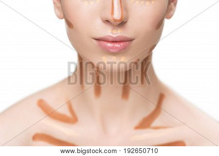 Young lady is using various foundations on clavicles. Focus on brown lines. Close up