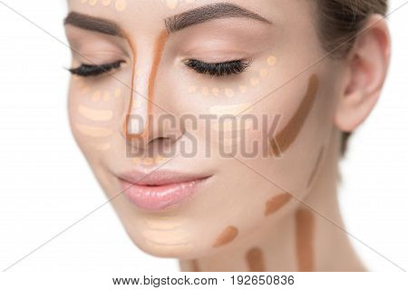 Attractive woman is drawing various lines on visage through different concealers. Close up portrait. Isolated