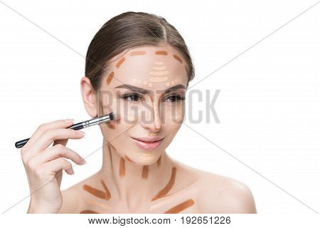 Confident attractive young lady has different correctors on face and going to create perfect tone though using special brush. Portrait. Isolated and copy space