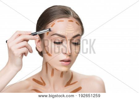 Concentrated pretty woman is using cosmetic tassel for shading various kinds of concealers on face. Portrait. Isolated