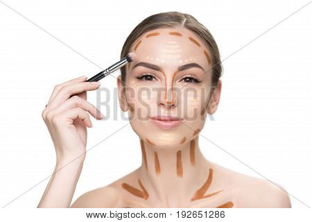 Interested pretty girl is shading concealers on forehead and looking at camera with light smile. Portrait. Isolated