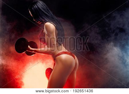 Side-view of muscular unrecognizable brunette with perfect body in bikini standing in front of black background with red smoke and holding dumbbells in her hands.