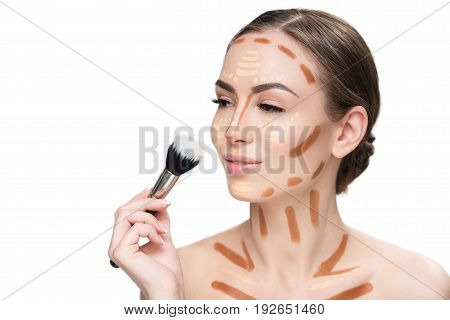 Confident lady is going to shade foundations at her pretty face. She looking aside wit light smile. Portrait. Isolated and copy space