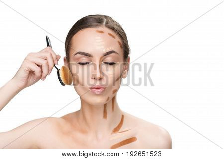 Pretty busy woman is using round tassel in order to shade various concealers on face. She closing her eyes. Portrait. Isolated and copy space