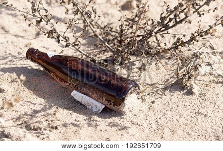 Glass bottles in the sand on nature. trash