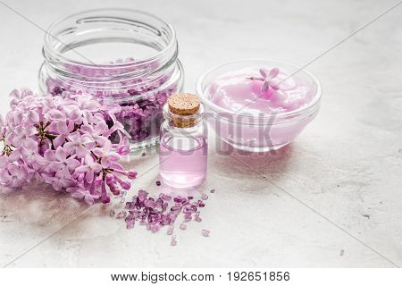take bath with lilac cosmetic spa set and blossom on stone table background